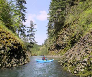 Kayak floating down a narrow river