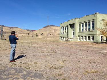 Man taking a photof of an abandoned building in the High Desert.