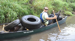 Boater with a boat load of tires and other garbage from a river clean up event