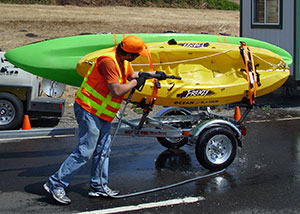 A boat being pressure washed to remove aquatic vegetation.