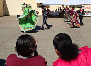 Two young women, shown from behind, watching a performance from a Mexican dance group
