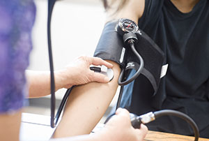 A nurse measuring the blood pressure of a youth