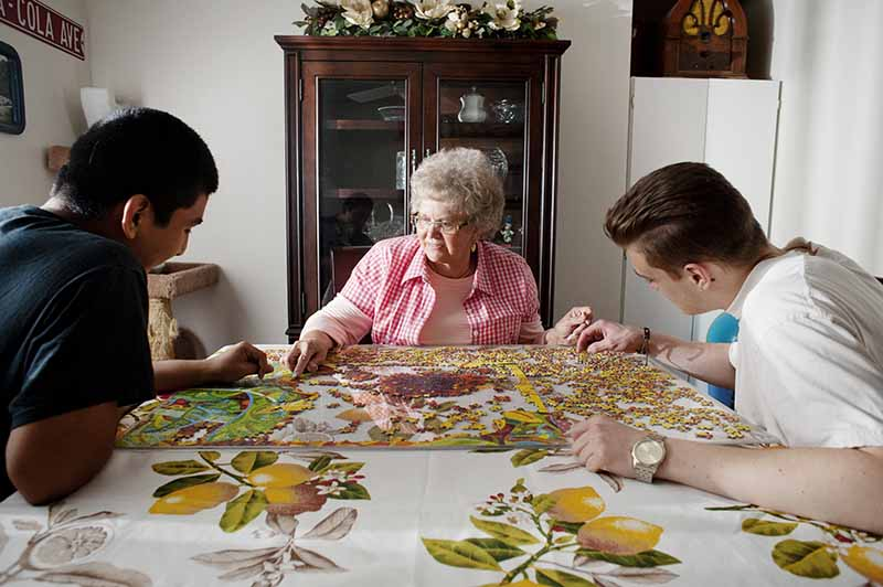 foster parent doing a puzzle at a table with two youth