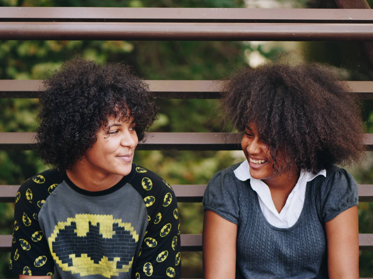 two Black teens sitting outside