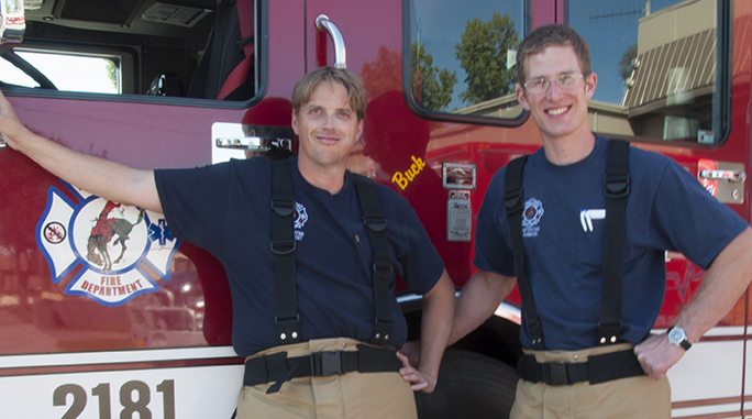 Firefighters standing next to fire truck