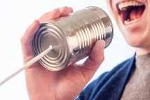 person talking in can and string phone