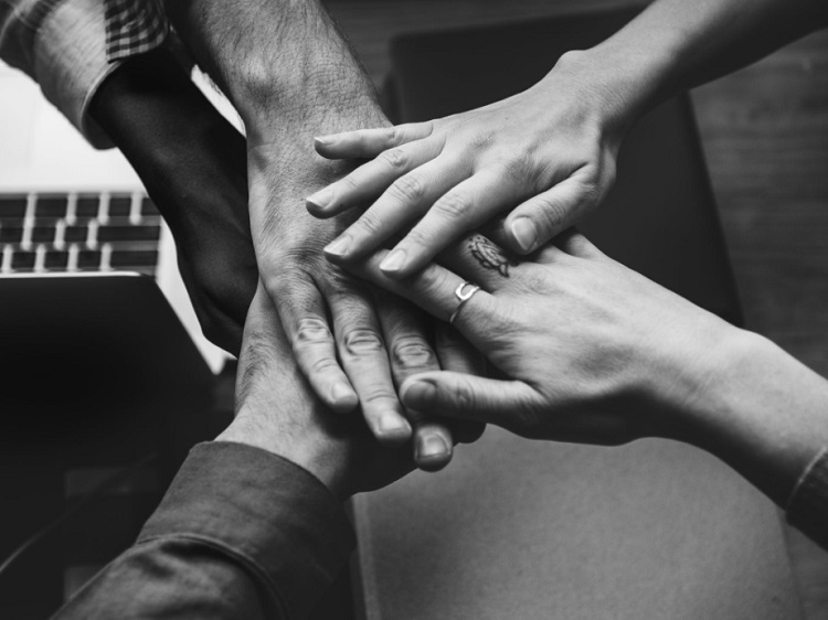 Monochrome photo of 5 hands coming together in team work