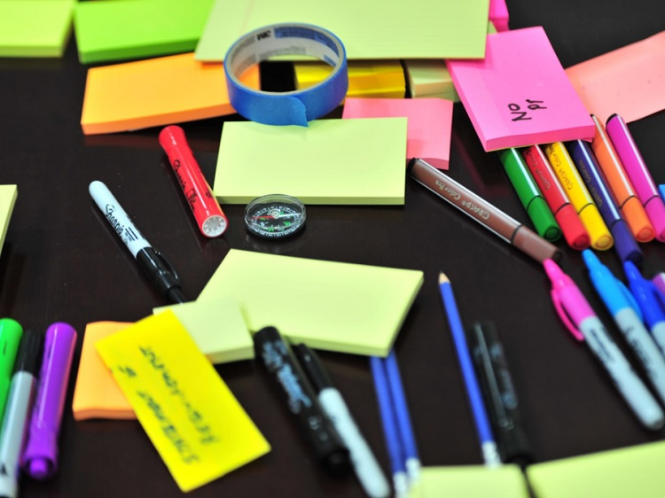 Sticky notes, colorful pens, a plastic compass and painters tape on a table.