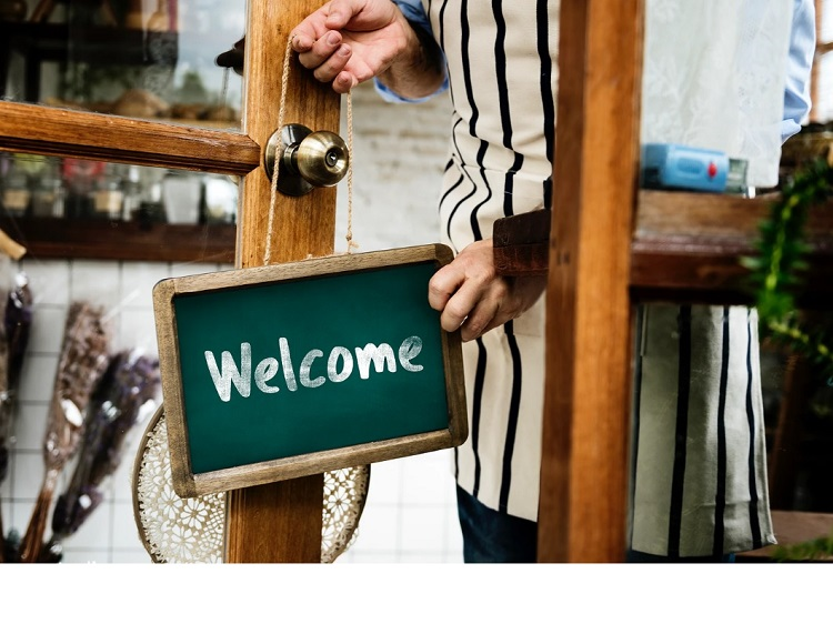 Welcome sign on door with hands either placing or removing sign